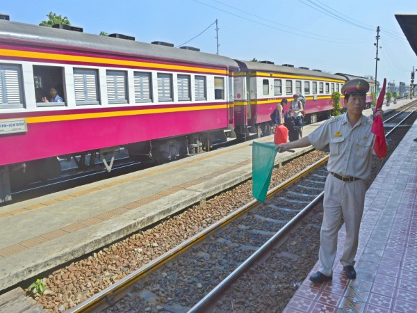 A Train-line in Thailand with a conductor waving