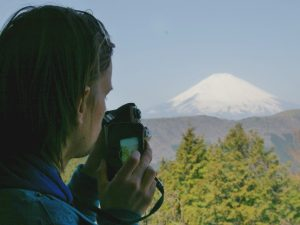 Man with camera looking at Mount Fuji Japan
