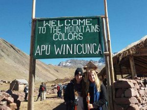 Women standing by sign for mountain trek Peru