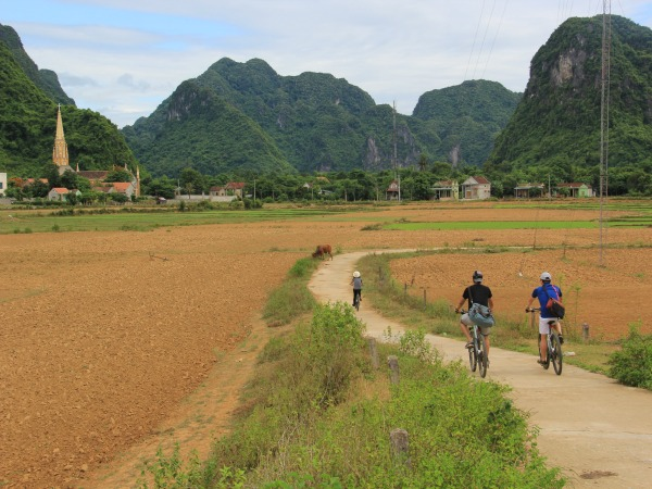 Two people cycling through landscape in Vietnam