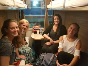 Women smiling in sleeper train cabin Vietnam