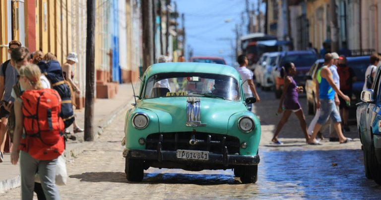 classic car in middle of road in havana