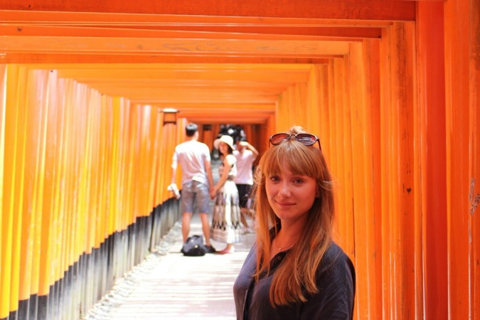 Woman standing under arches in Kyoto Japan