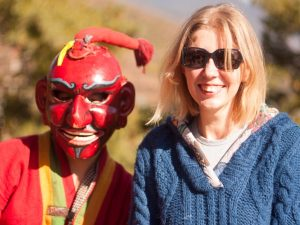 Kate standing with a clown at Bhutanese festival