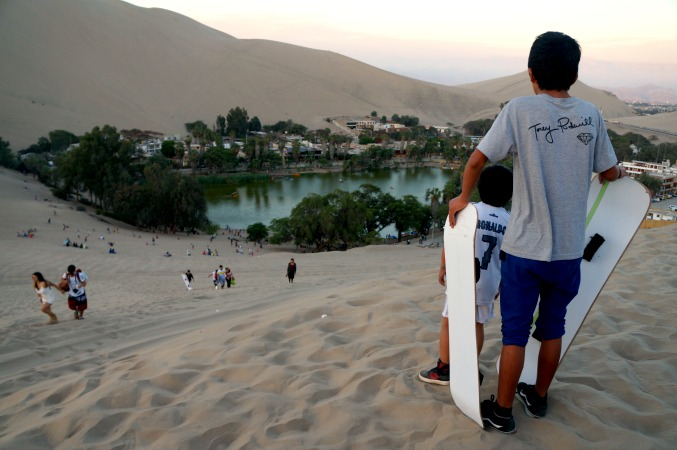 boy holding sand boards in haucachina