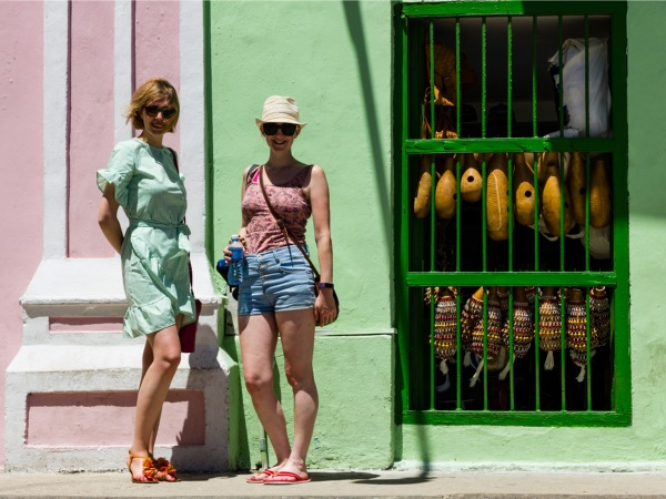 Travellers standing outside local shop in Havana