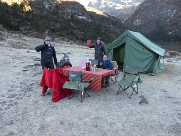 People gathered at campsite drinking tea