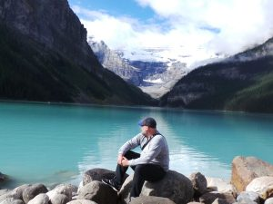 Man looking out to lake louise whilst pearched on rock
