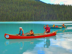 group of people in traditional Canadian open canoes on emerald green lake