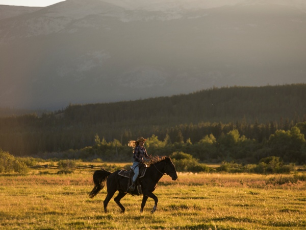Women riding a horse through the Cariboo