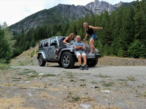 family sitting on car in canada