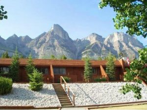 View of a log cabin with mountains in the background