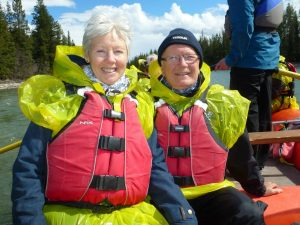 Smiling couple wearing life jackets ready to canoe in Canada