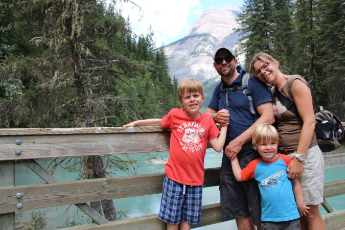 Family holding hands and smiling in a national park