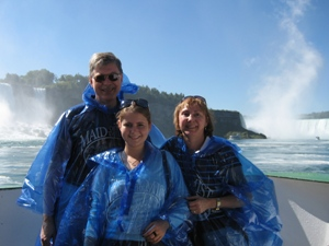 Family wearing blue ponchos on boat with Niagara in the background