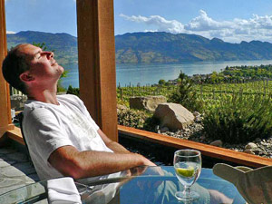 Person enjoying sunshine and wine in Okanagan Valley Canada
