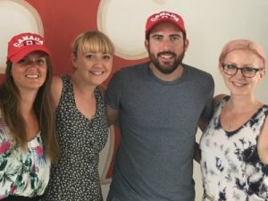 Team of smiling people wearing Canada baseball caps