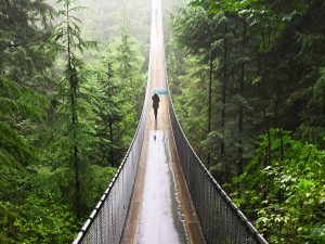woman walking along suspension bridge in canada