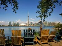 People sat on chairs looking out the Toronto buildings
