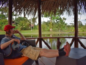 man relaxing while he stares at the jungle