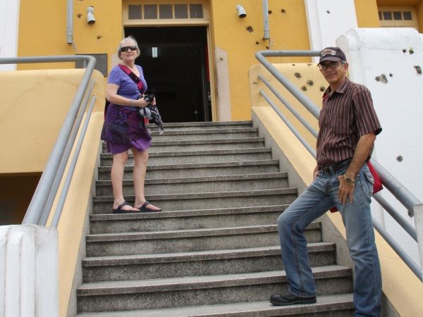 Couple standing outside steps in Cuba