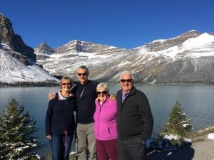 Group of adults standing in front of Canadian lake and mountains