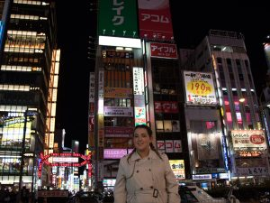 Woman standing in front of neon-lit buildings in Tokyo, Japan