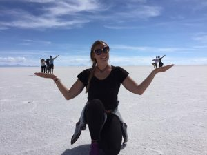 Woman in salt flats with people appearing to stand on her hands