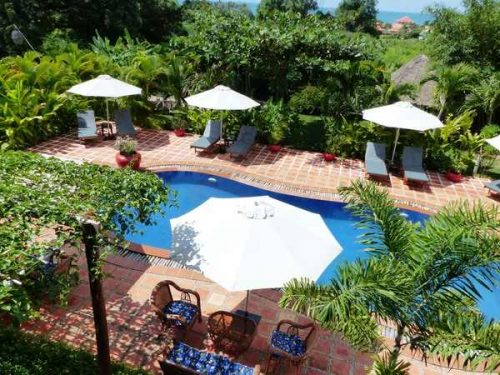 Blue pool and white umbrellas at Raingsey Bungalows in Kep