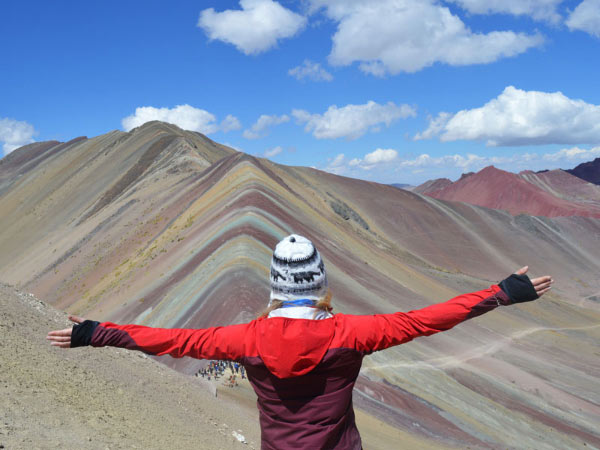 A lady traveller facing the Rainbow mountains in Peru
