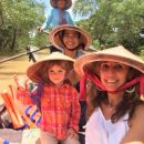 family in the mekong delta sailing down the river on a wooden boat