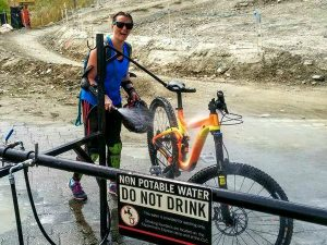 Woman cleaning mountain bike with hose in whistler canada