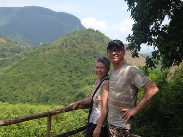 Couple smiling on bridge with green view