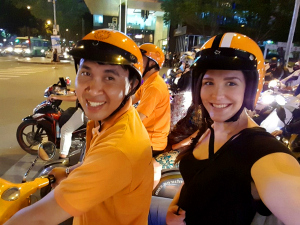 customer riding on the back of a vespa scooter with driver