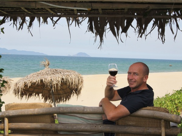 Man holding wine glass up with beach setting