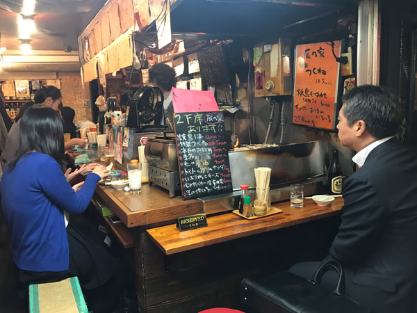 Locals sitting at a small izakaya in Tokyo drinking and eating