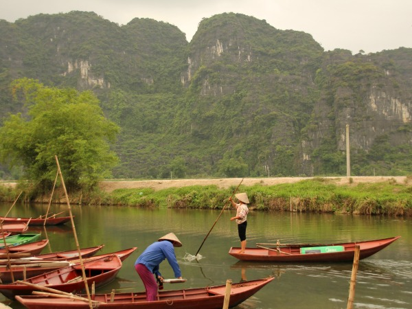 Locals standing on rowing boats in Vietnam