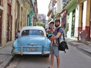 Father and son smiling next to Classic Car in Cuba