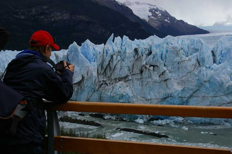 Man in red cap taking picture of glacier