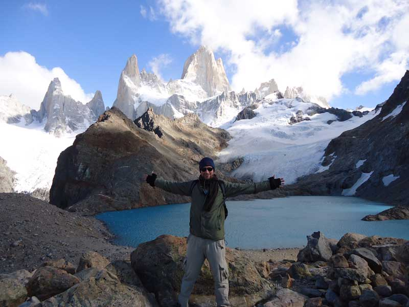 Man with arms wide open in front of glacier