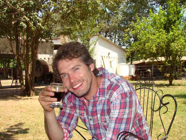 man smiling with glass of red wine
