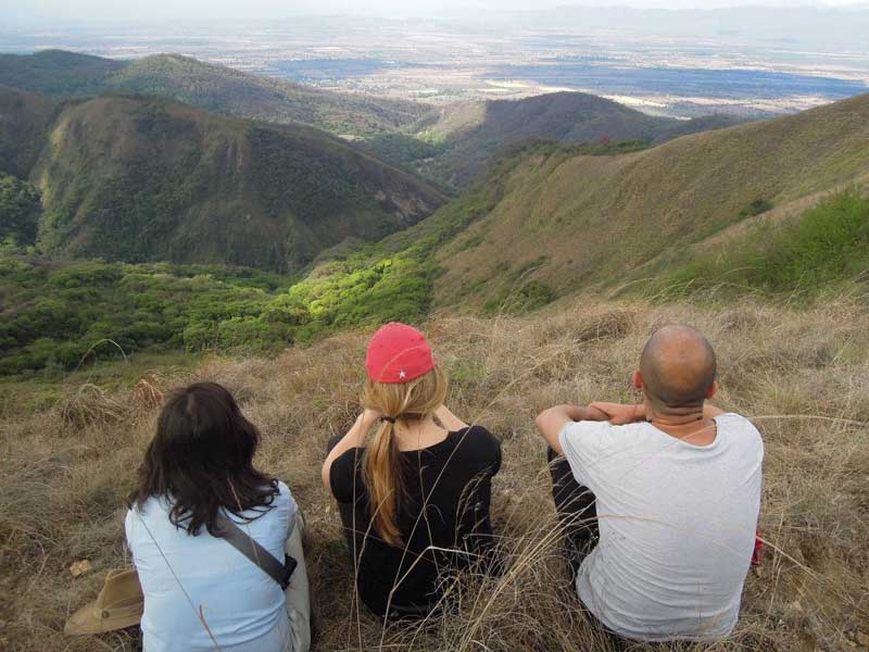 3 people sitting up high and looking at mountains