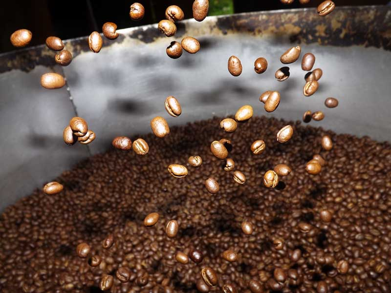 Coffee beans being poured into a tin