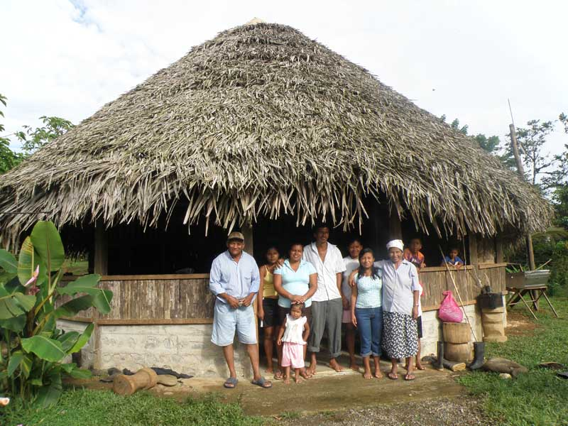 Tribe of locals smiling in front of hut