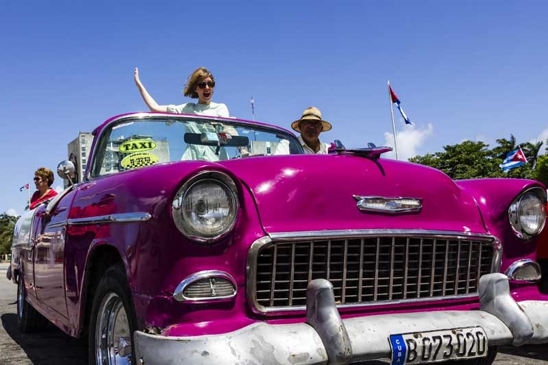 woman standing in pink classic car