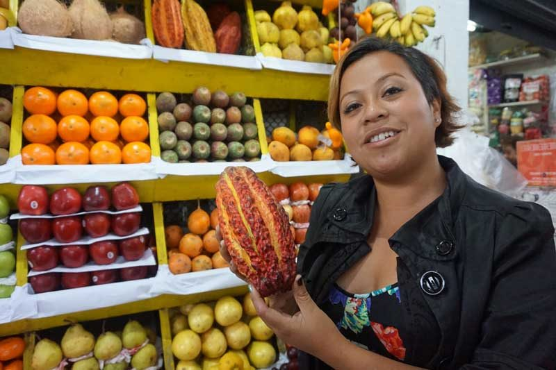 Woman holding up fruit in a fruit market Lima