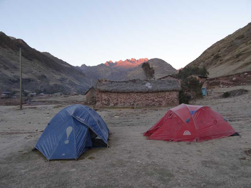 Two tents sitting on top of mountain with sunrise