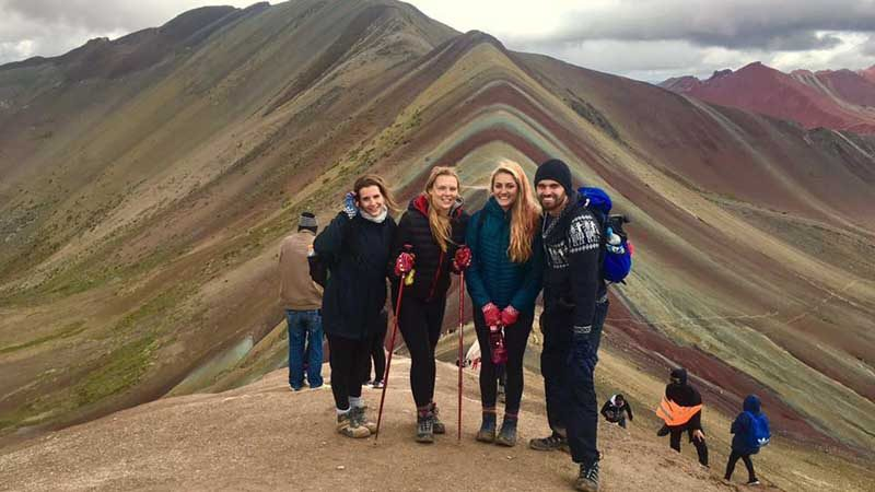 people standing by rainbow mountain