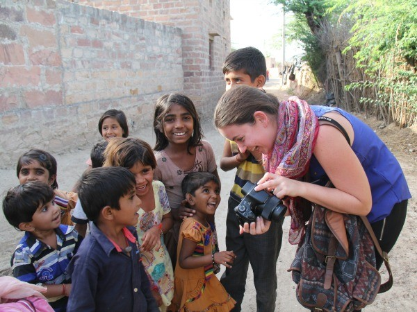 Woman showing local children picture on camera