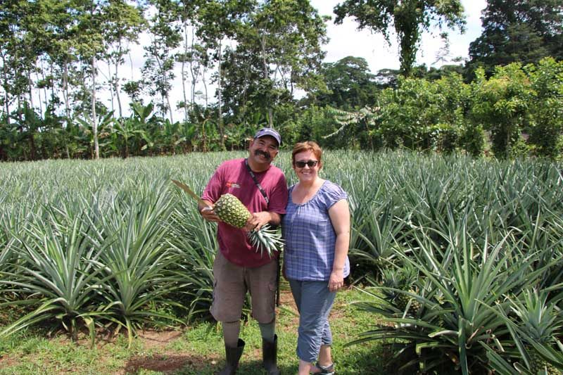 Woman standing with local guide and huge pineapple